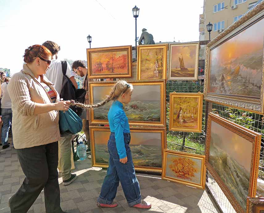 Middle-aged woman holding a plait of elementary age girl trying closer look at the picture on the street exhibition and sale of paintings in the city core during the celebration of the City Day