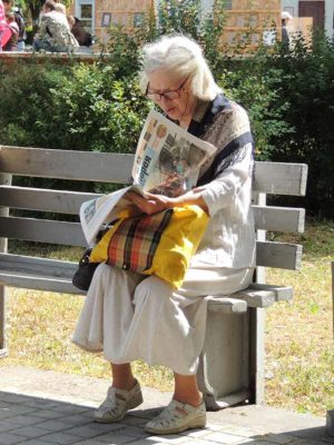 Gray-haired lady with glasses reading the newspaper on a park bench