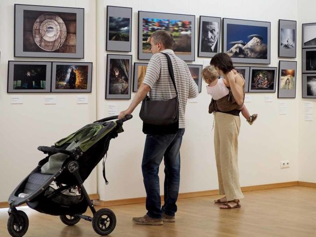 Family with elementary age girl and pram in a gallery. Classic Photo Gallery. Russian Week Of Photography 2016