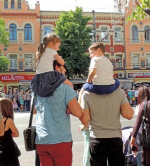 Communication of elementary age girl and boy sitting on fathers shoulders. City dwellers on the parade of Street Theatres on the Platonov Arts Festival