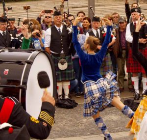 "Girl dancing during a performance of Celtic pipes and drums band surrounded by townspeople in the Park of arts ""Muzeon"" on the Crimean embankment, Moscow. Festival of military orchestras ""Spasskaya Tower""."