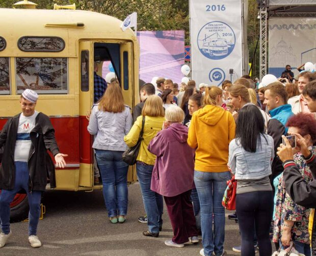 Townspeople stand in a queue for to see the inside of the retro bus interior. Festive occasion of the Moscow bus on the Frunze Embankment