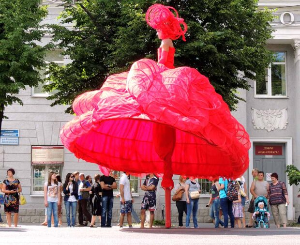 Actor in red costume on stilts on the avenue. Parade of Street Theatres on the Platonov Arts Festival