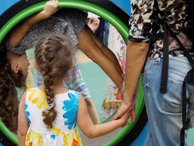 Elementary age girl with plait and man holding hands standing near the children's centrifuge